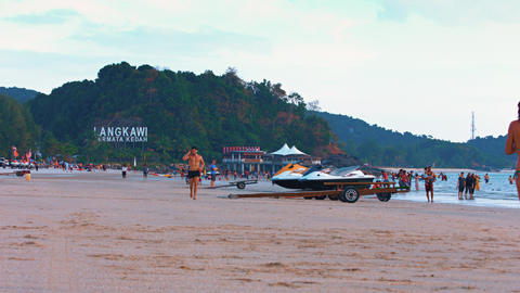 Tourists enjoying an afternoon on a popular tropical beach in Langkawi. Malaysia Live Action