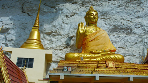 Big. gold colored buddha statue outside Wat Tham Kisap. a Thai temple in Langkaw Footage