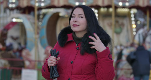 Portrait of adult Caucasian woman in red coat putting on hood. Positive adult Live Action