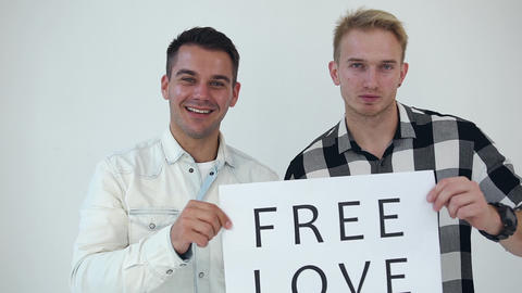 """Front view of handsome smiling two men which posing on camera with poster """"Free Live Action"""