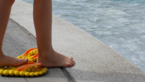 Child is trying water in the pool. Flip flops by the pool and feet in the water Live Action
