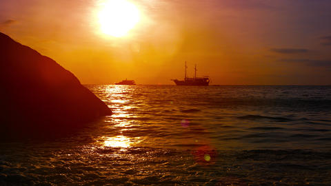 Sunset Seascape with Waves and Boats under a Red Sky Footage