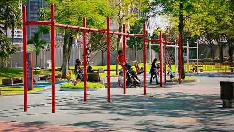 Children playing on the swings at Kuala Lumpur City Park in Malaysia Live Action
