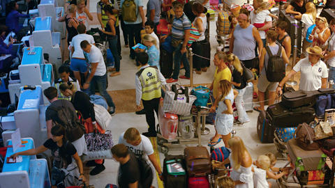 Airline travelers. checking in their bags at the departure counter Footage