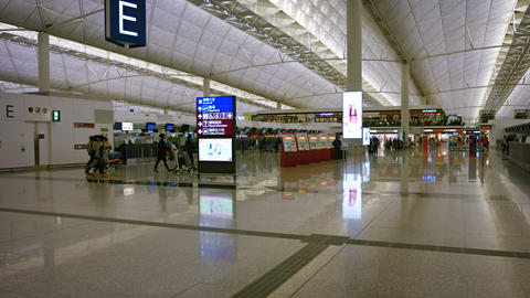 Passengers strolling through the departures area of the terminal Footage