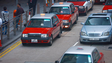 Taxi and other vehicle traffic on a busy urban street in downtown Hong Kong Footage