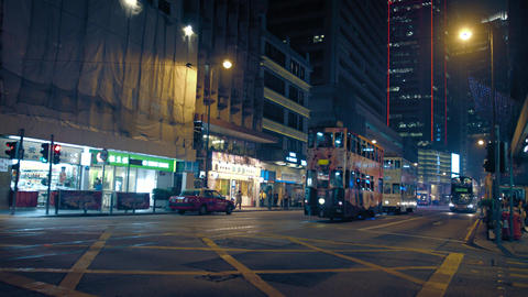 Urban intersection with electric street cars and buses in Hong Kong. at night Footage