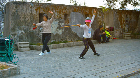 Women participating in Tai Chi training with weapons in a city park in Macau Footage