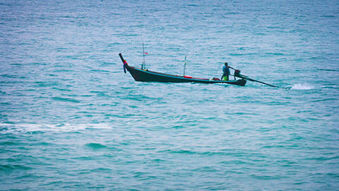 Boatmen Pilot their Fishing Boat through a Calm. Tropical Sea Footage