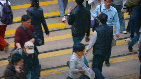 Pedestrians crossing a busy urban street in downtown Hong Kong Footage