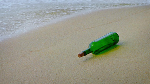 Green glass wine bottle rolls in the gentle waves on a sandy tropical beach. wit Footage