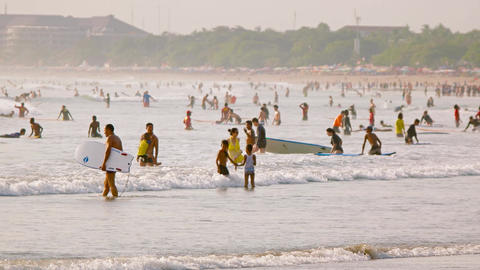 Surfers. body boarders and swimmers crowd into the water off Kuta. Bali Footage