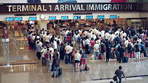 Long lines of travelers at the immigration counters in arrivals area Footage