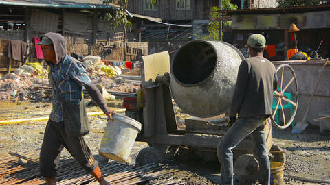 Manual laborers pouring dry cement into a diesel mixer. Myanmar Live Action