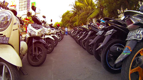 Motorbikes parked in long rows in a downtown area of Kuta. Bali Footage
