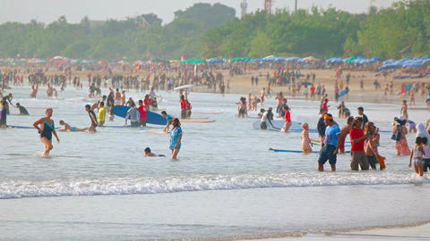Local people and tourists enjoy on crowded Kuta beach Footage