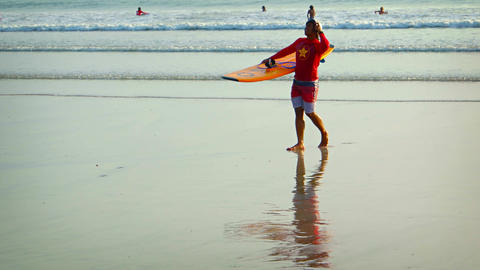 Surfer in red dress and halmet get out the sea with yellow surfing board Footage