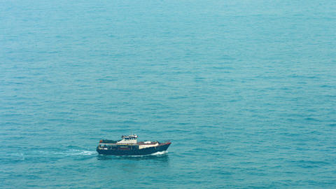 Small commercial fishing boat cross blue sea water from left to right Footage