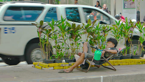 Homeless man sleeping in a salvaged lawn chair on the street in Bangkok Footage