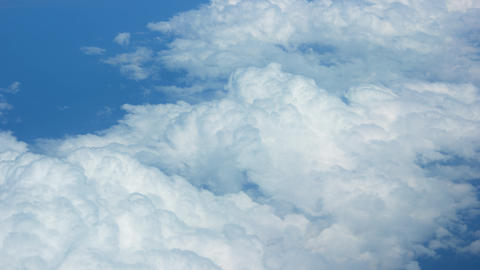 Airborne view of puffy clouds from above Footage