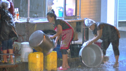 Street vendors scrubbing pots in the hevy rain in downtown Bangkok Footage