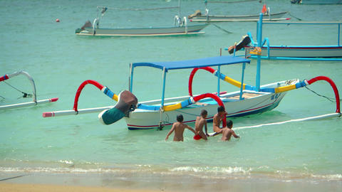 Local children swimming in ocean and climbing on outriggers of boat Footage