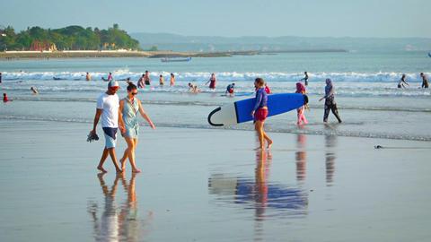 Man surfer with big surfing boat walks on a popular balinese Kuta beach Footage