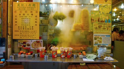 Steam rises from cooking food in the kitchen of a noodle shop in Hong Kong Footage