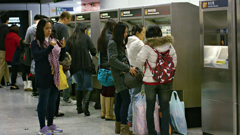 Commuters purchasing tickets at electronic vending machines in subway station Footage