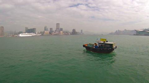 Public utility boat. cruising slowly through a Hong Kong bay under a cloudy sky Footage