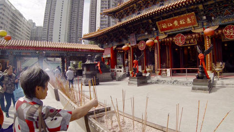 Buddhists praying and offering incense at Wong Tai Sin Buddhist temple Footage