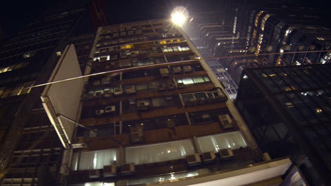 Tracking shot of highrise buildings towering above at night Footage