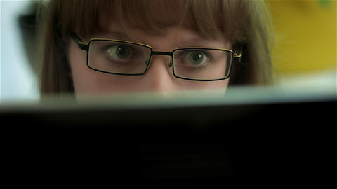 4K Girl With Eyeglasses Surprised by Something, Seen on Computer Monitor Footage