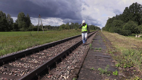 Railroad worker with adjustable wrench walking near railway Live Action