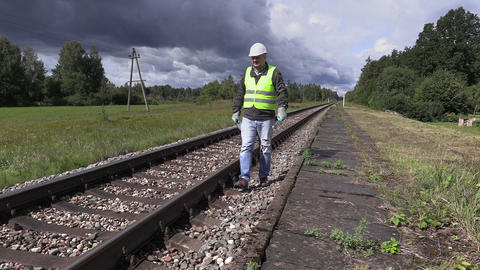 Railroad worker with cell phone and adjustable wrench walking near railway in sl Live Action