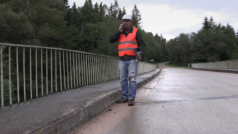 Worker talking on cell phone on bridge Footage