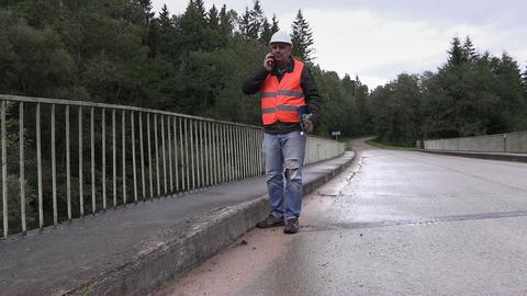 Worker talking on cell phone on bridge Footage