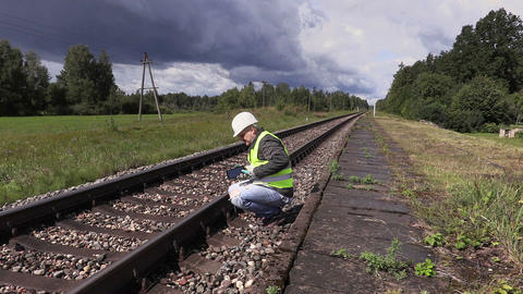 Railroad worker using tablet PC and walking near railway Live Action