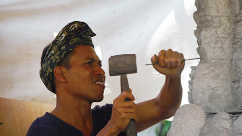 Local. Balinese sculptor. chipping at and shaping a block of stone Footage