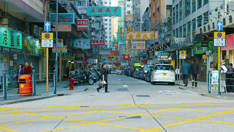 Pedestrians and parked cars on a busy. commercial street in Hong Kong. China Footage