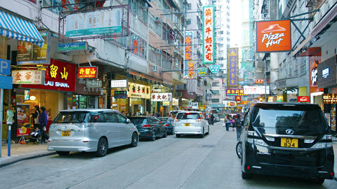 Western and Chinese businesses on a busy commercial street in Hong Kong Footage