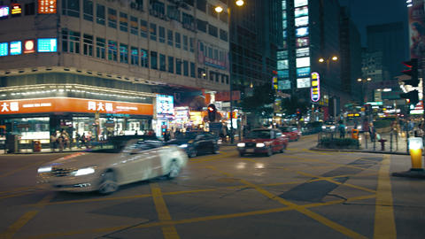 Urban intersection with pedestrian and vehicle traffic at night in Hong Kong Footage