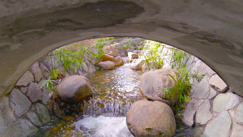 Decorative Stream Flows around Boulders and Under Bridge. with Sound Footage