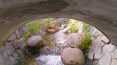 Decorative Stream Flows around Boulders and Under Bridge. with Sound Footage
