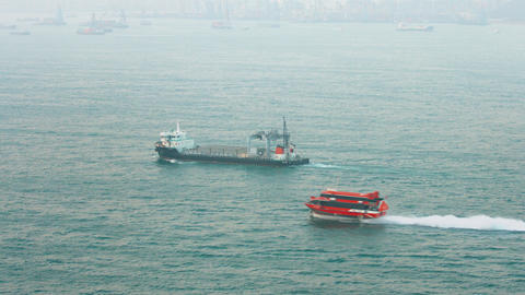 Commercial cargo ship and a speed ferry cruise through bay off Hong Kong Footage
