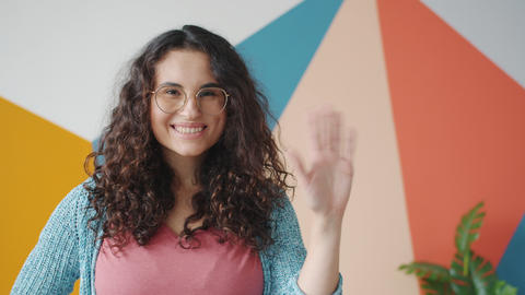 Smiling young lady in glasses waving hand meaning hello attracting attention Live Action