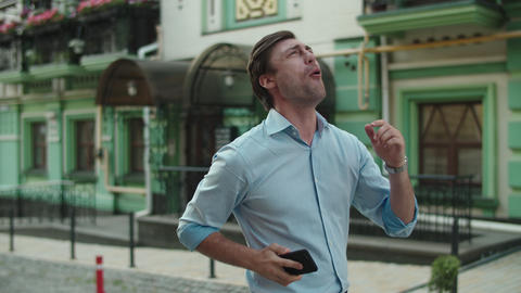 Excited man dancing with phone at street. Joyful businessman celebrating victory Live Action