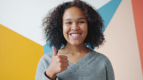 Attractive Afro-American woman showing thumbs-up gesture with glad smile Live Action
