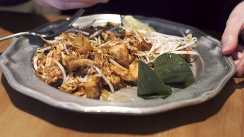 Girl sprinkles sugar on famous Thai dish - Pad Thai with noodles, chicken, tofu Live Action