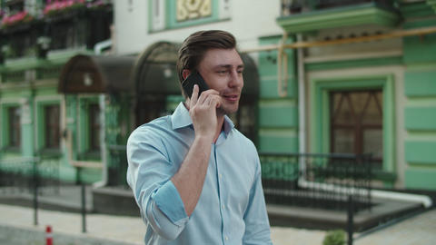 Happy businessman celebrating victory with mobile phone at street Live Action